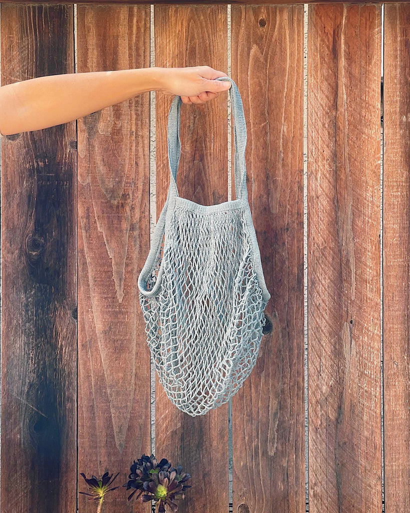 model holding blue cotton market tote shown against brown fence