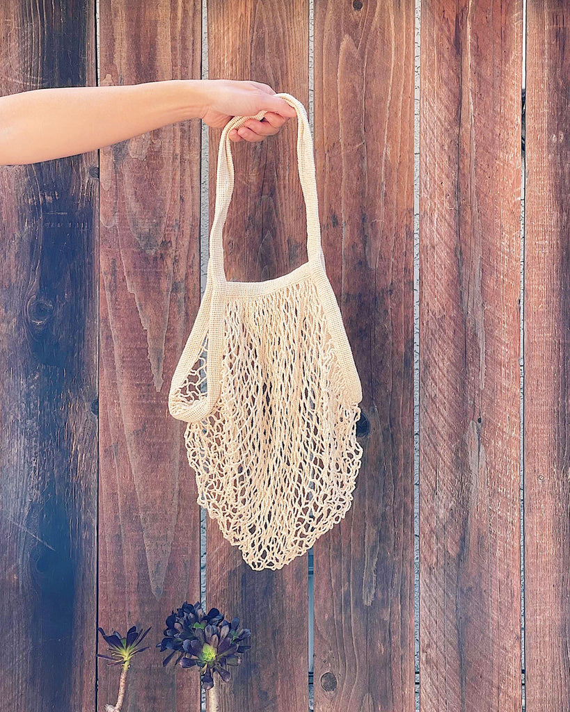 model holding ivory cotton tote shown against brown fence