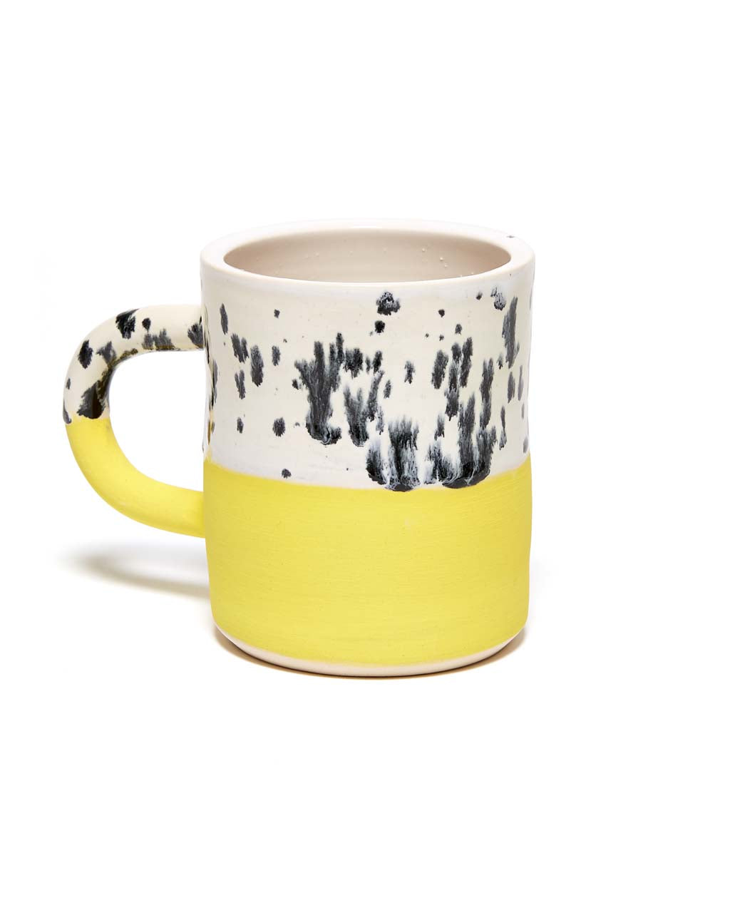 This mug features a two-tone design, with black dots on top and yellow on bottom.