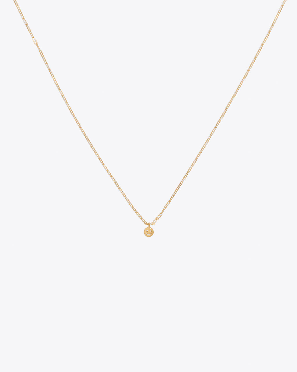 Gold necklace with a small smiley face pendent