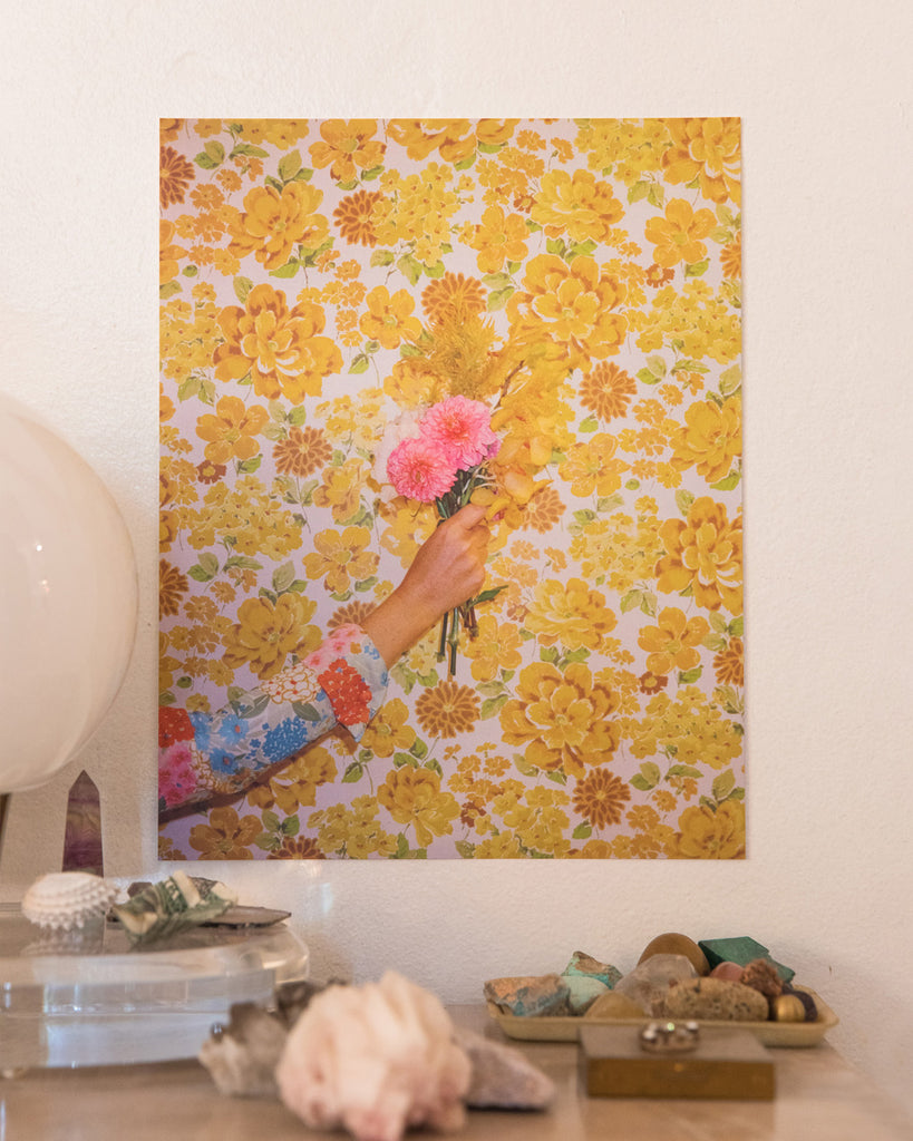 vintage yellow floral art print that features a hand holding a couple of pink flowers