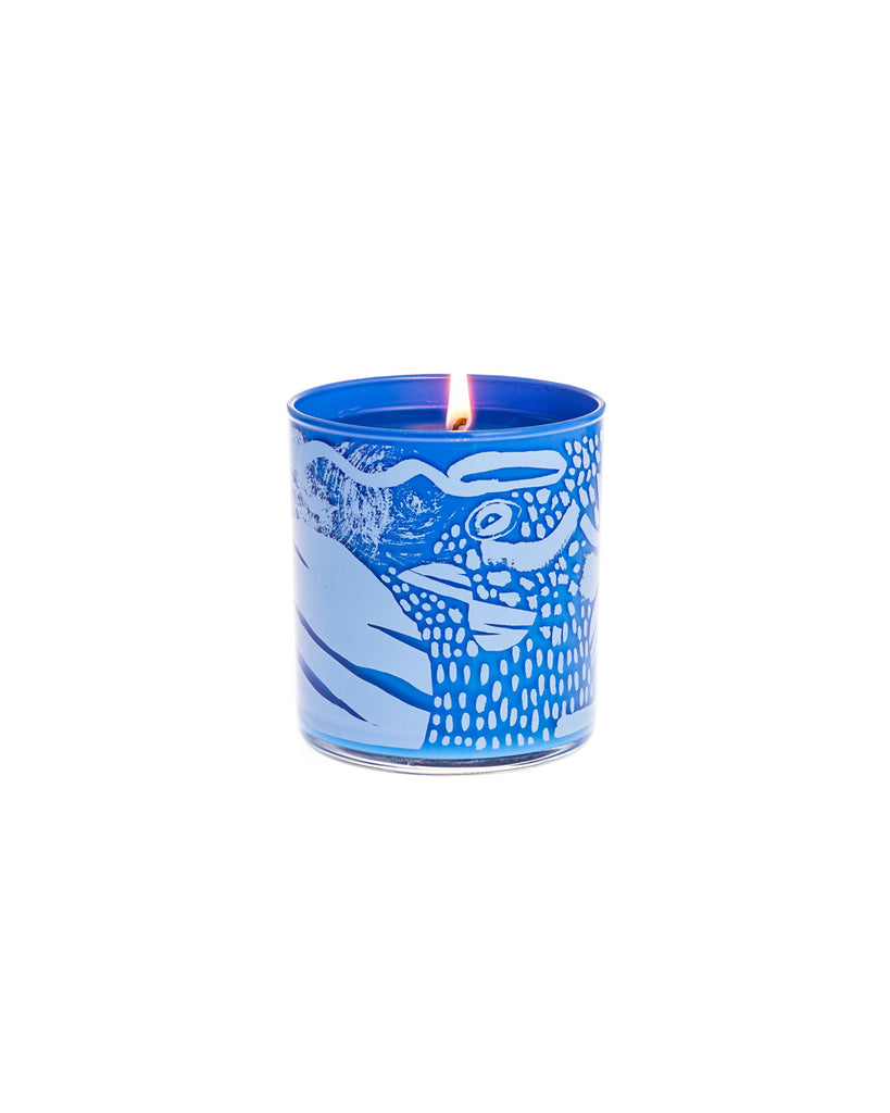 This Pironii candle comes in a blue tumbler with light blue art.