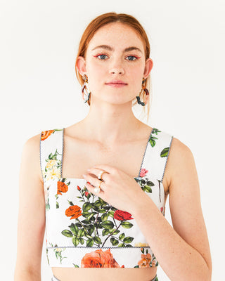 Fitted white crop top with a floral print shown on model