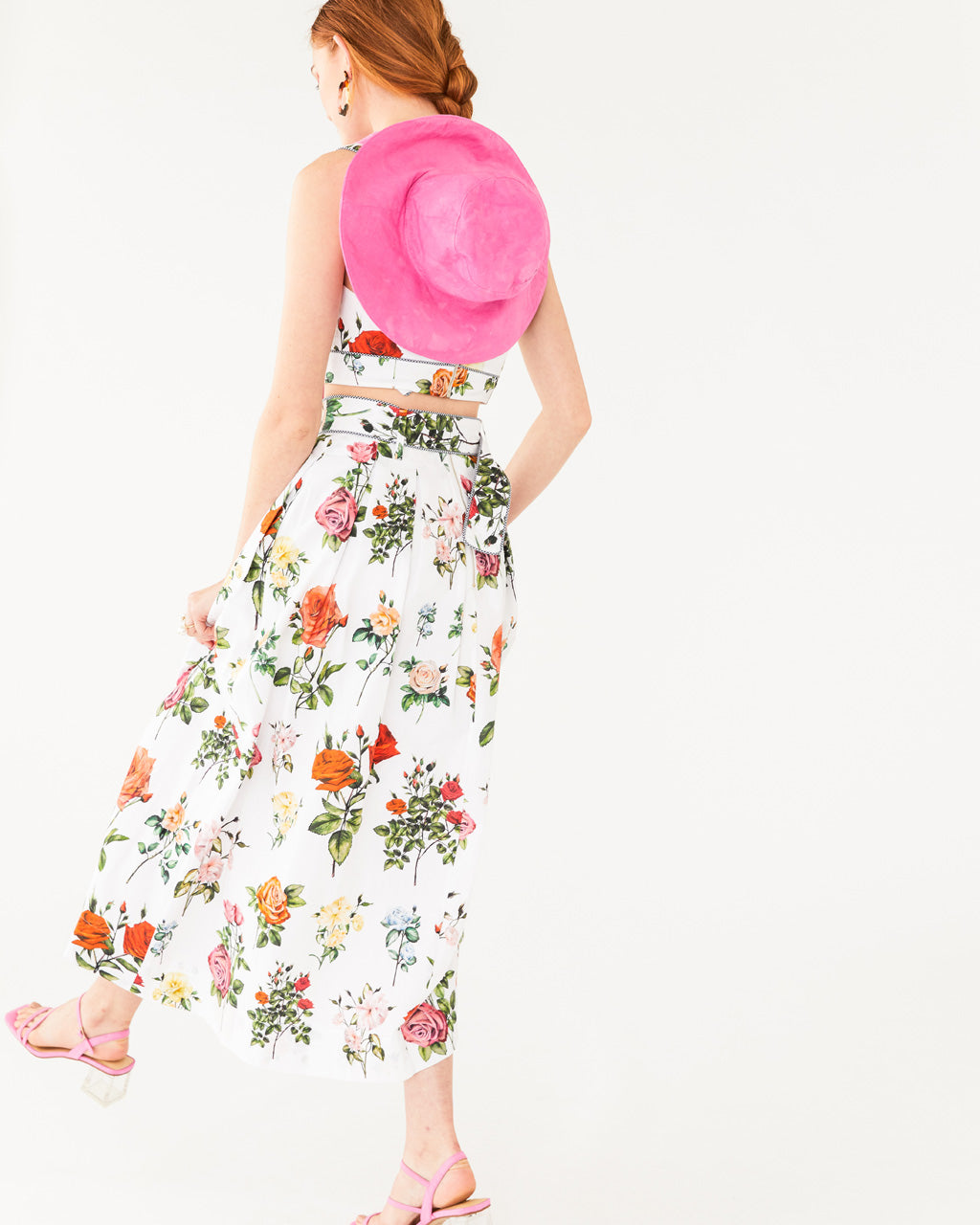 white midi skirt with an all over floral pattern paired with matching tank and bright pink hat shown on model