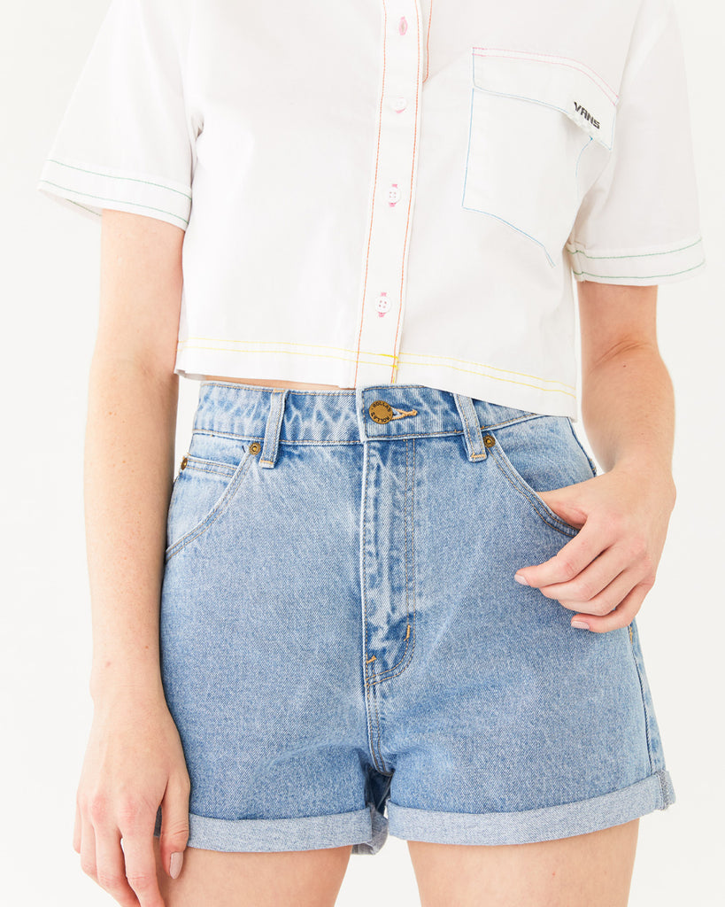 high rise light denim shorts with a cuffed bottom paired with a white crop button-up shirt