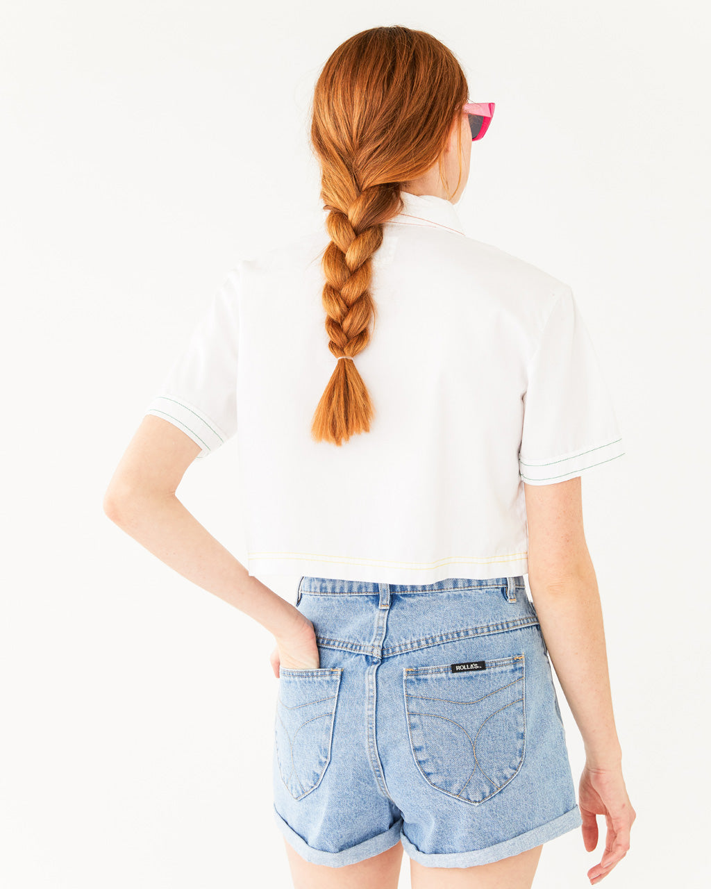 back view of high rise light denim shorts with a cuffed bottom paired with a white crop button-up shirt shown on model