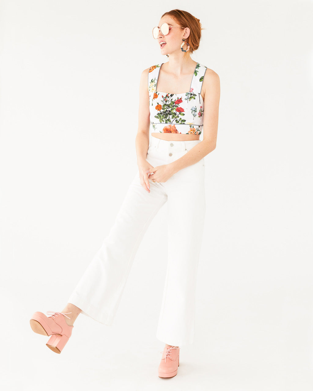vintage white wide leg ankle jeans paired with a pink heeled shoe and a white floral top shown on model