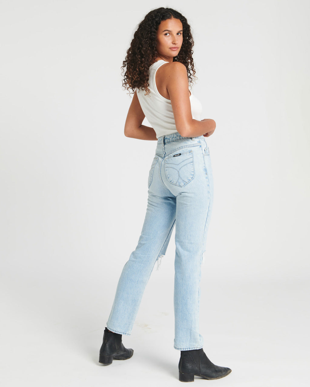 model wearing white tank top with lightwash worn jeans with black boots
