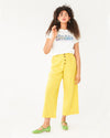 model wearing yellow ankle length pants with a grid design and paired with a white graphic tee