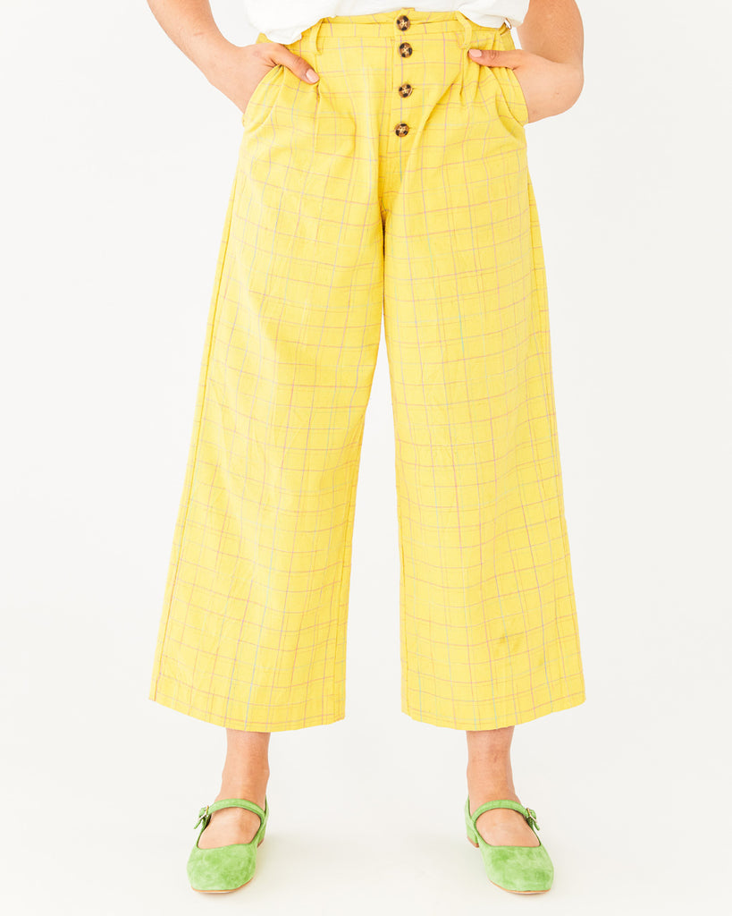 lower body shot of model wearing yellow ankle length pants with a button fly and a grid design paired with green shoes