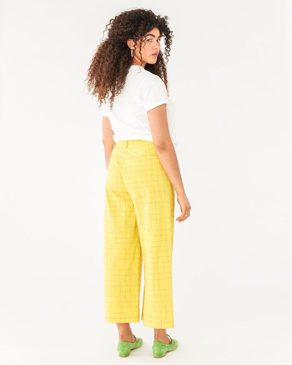 back shot of model wearing yellow ankle length pants paired with a white tee and green shoes
