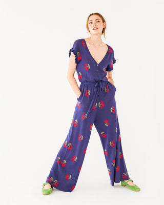 model wearing a dark purple short sleeve jumpsuit with a cherry design all over and a cinched tie waist with green shoes