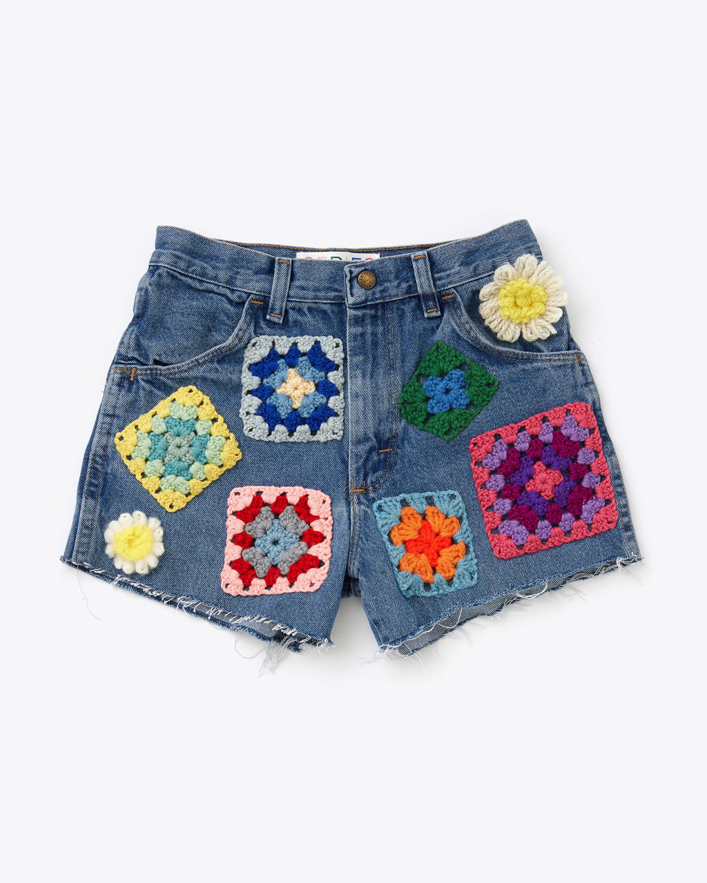 front side of medium wash denim cut off shorts with 6 multicolored crochet squares and 2 crochet flowers patched all over.