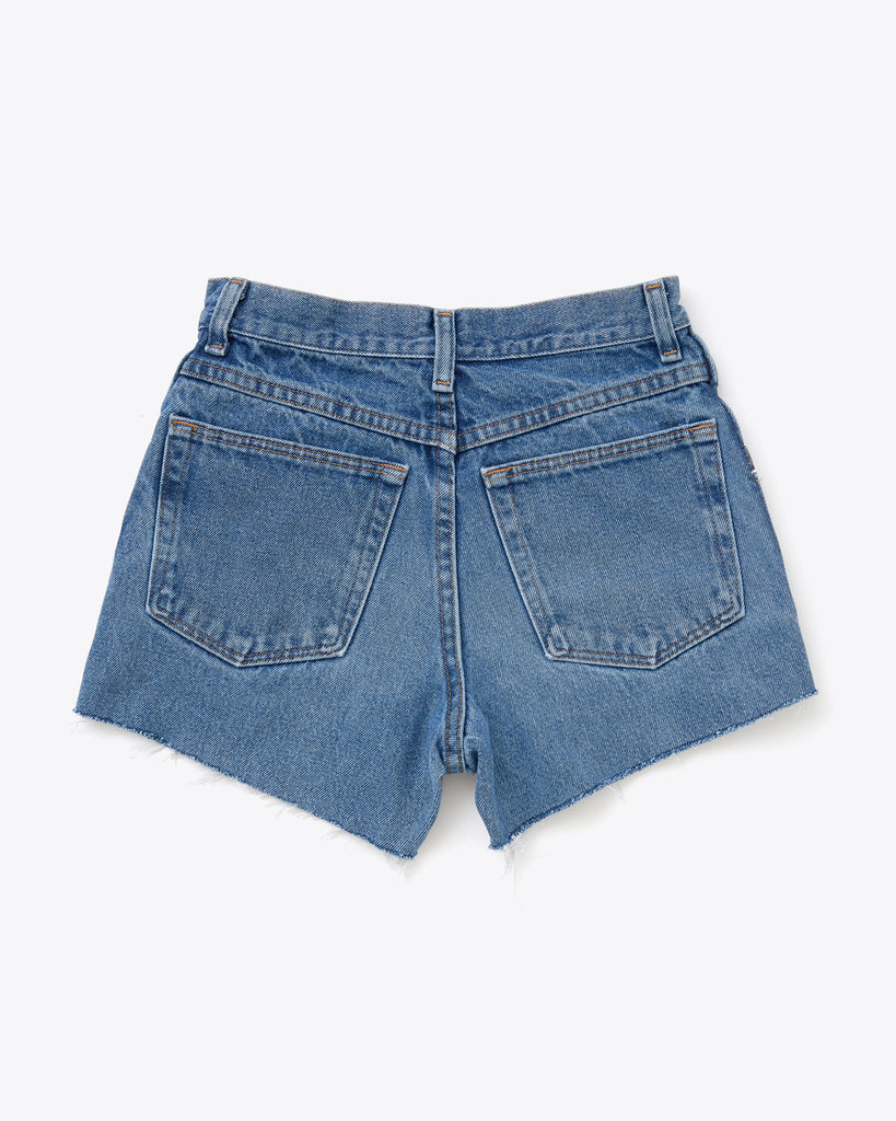 back side of medium wash denim cut off shorts with two pockets.