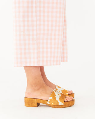 tan cow print clogs featured on a model