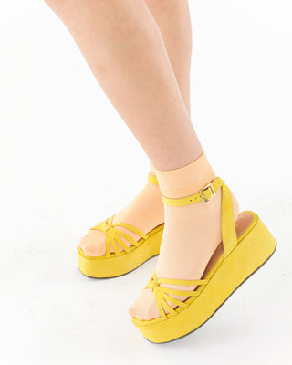 model wearing yellow platform sandals with peach colored socks