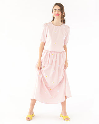 brunette model wearing light pink daisy embroidered skirt paired with matching top