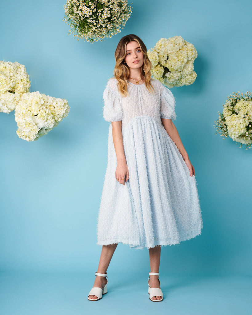 model wearing oversized midi dress with puff sleeves in sky blue and white heels