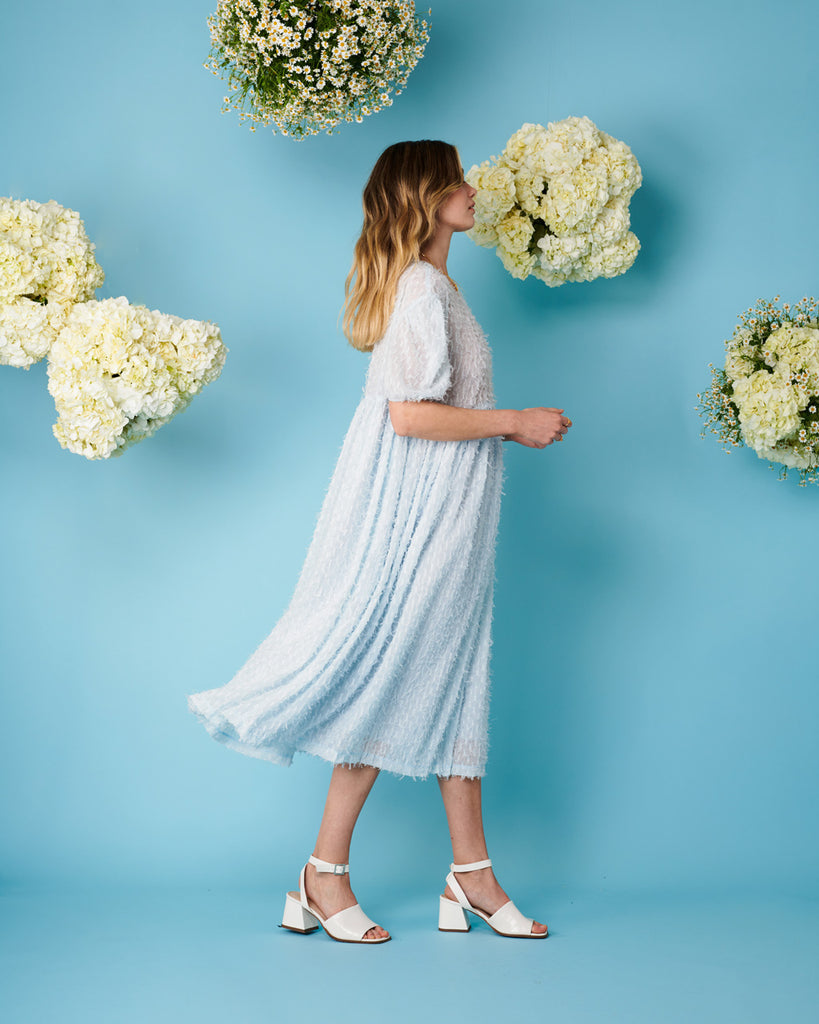 side view of  model wearing oversized midi dress with puff sleeves in sky blue and white heels