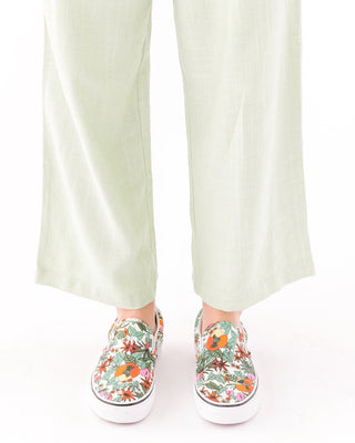 white classic vans slip ons with a tropical floral pattern shown on model wearing mint green pants.