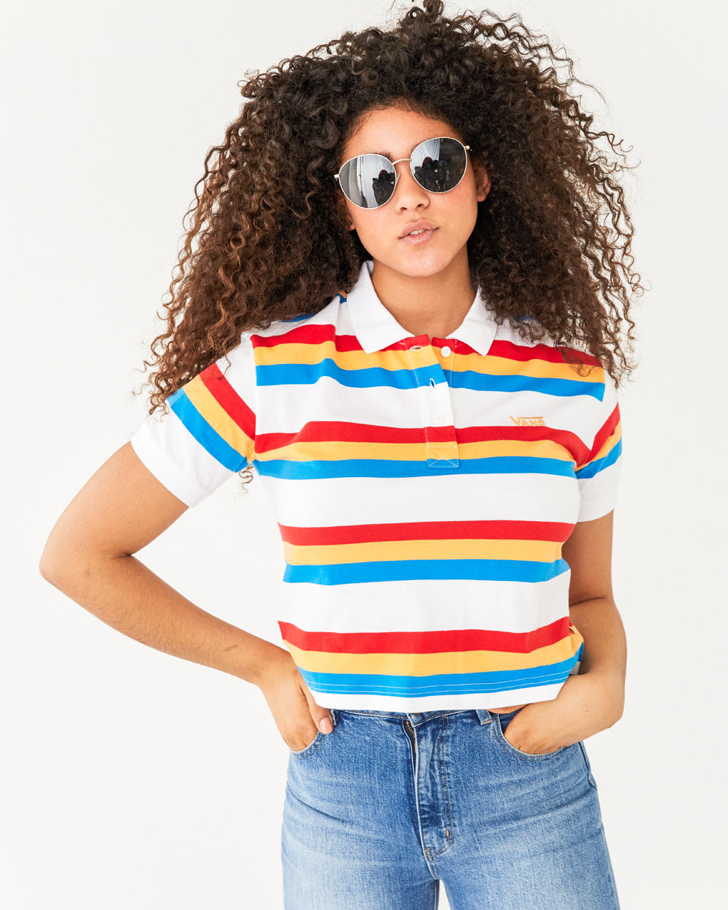 upper body shot of model wearing a white vans polo with red, yellow, and blue stripes paired with light wash denim