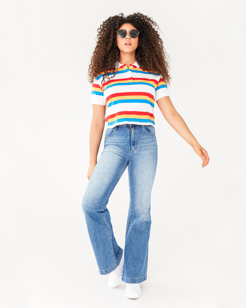 full figure shot of model wearing a white polo with red, yellow, and blue stripes paired with a light flare jean and white tennis shoes