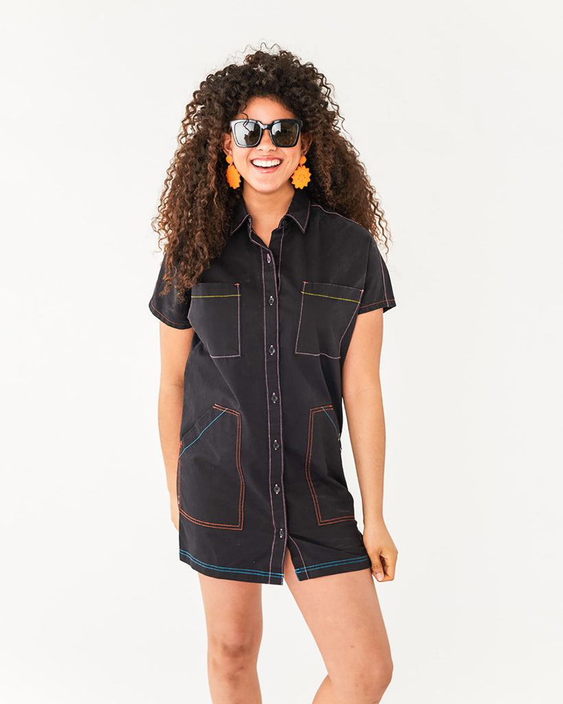 woman wearing a black shirt dress with multi-colored contrast stitching