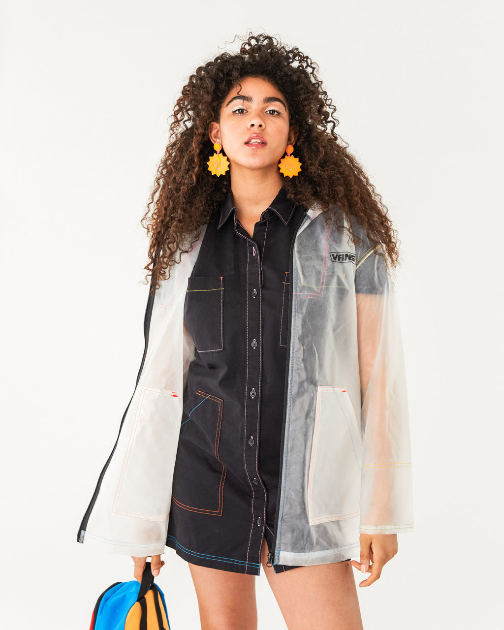 clear rain jacket with black zipper trim paired with a black jean dress shown on model