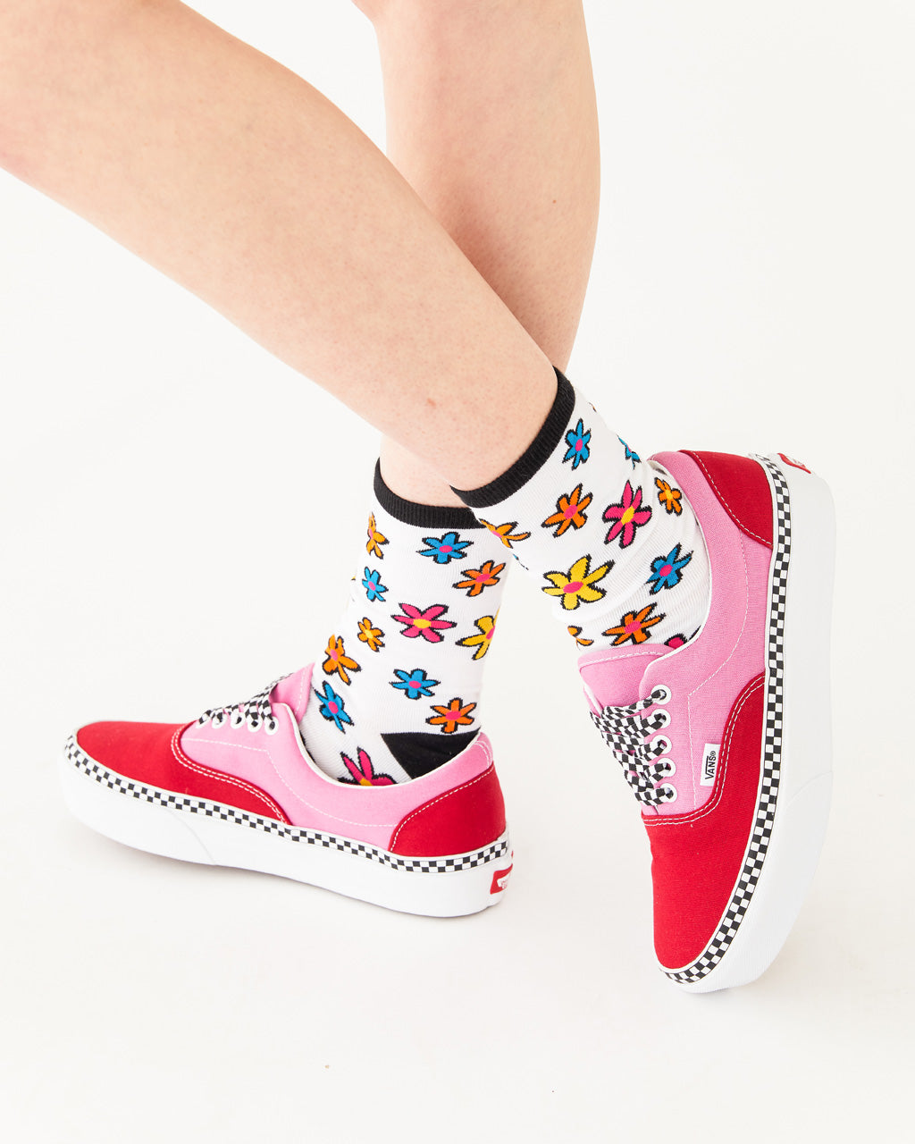 white above the ankle socks with a multi flower pattern and a black heel, toe, and band shown on model wearing pink vans