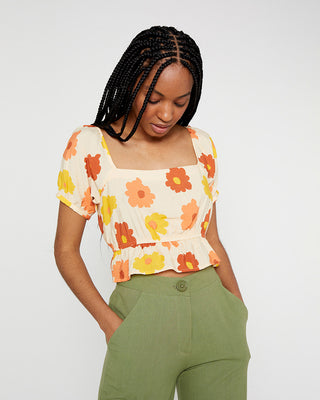 model wearing crop shirt with red, orange, yellow floral pattern and green pants