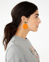 Large acrylic orange shaped earrings shown on model