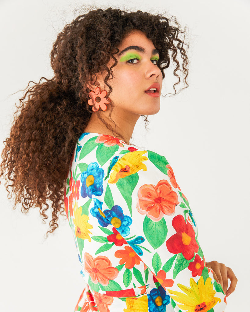orange mod flower posts featured on a model wearing a bright floral top
