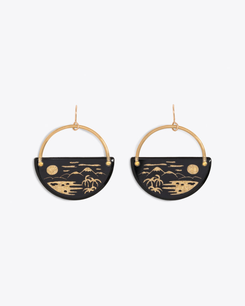 Gold hoop earrings with a half moon piece featuring a tropical landscape