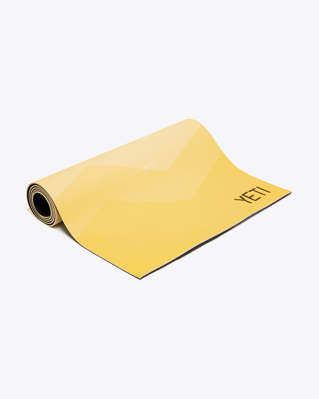 yellow yoga mat shown almost rolled up