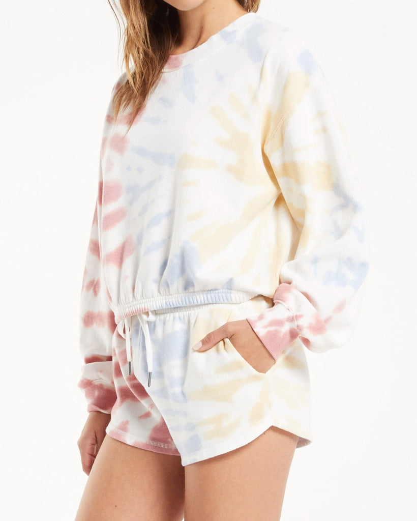 model wearing white sweatshirt with pale red, blue, yellow tie dye and matching shorts