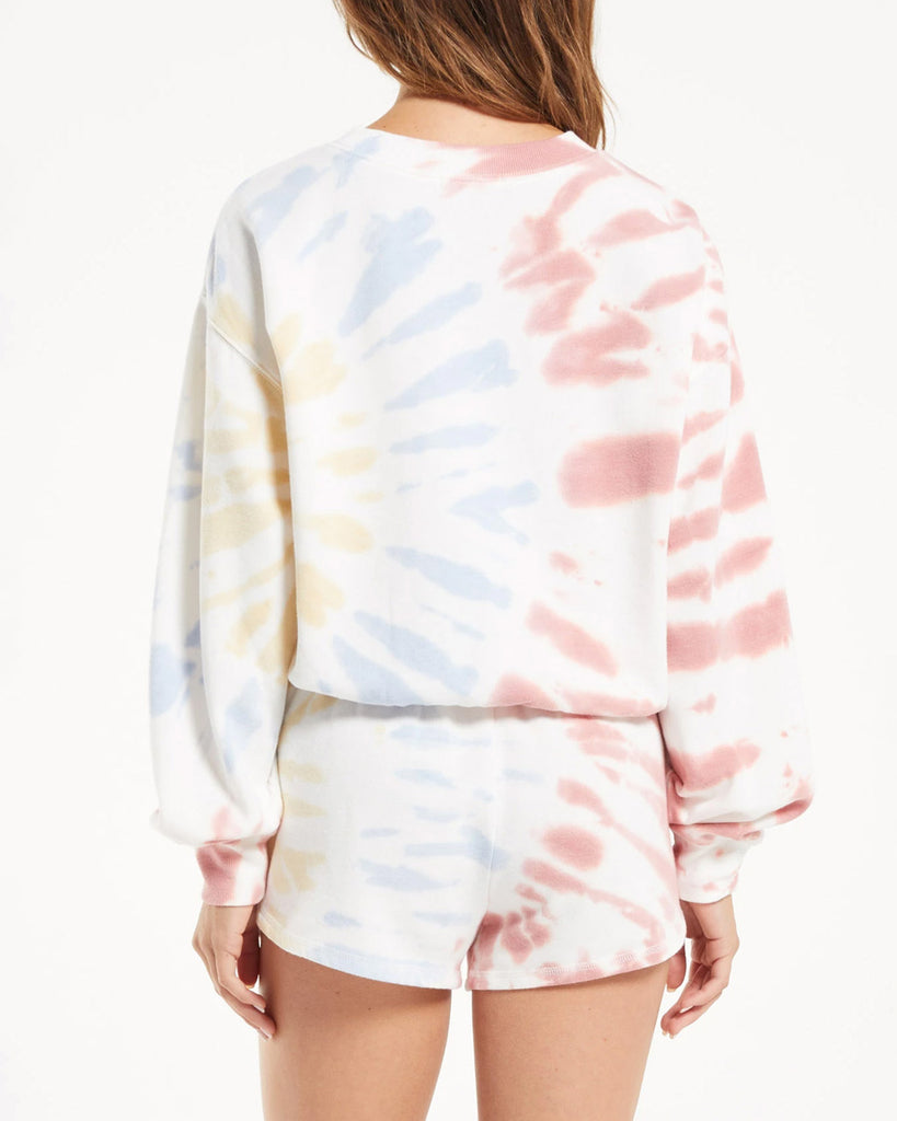 back view of model wearing white sweatshirt with pale red, blue, yellow tie dye and matching shorts