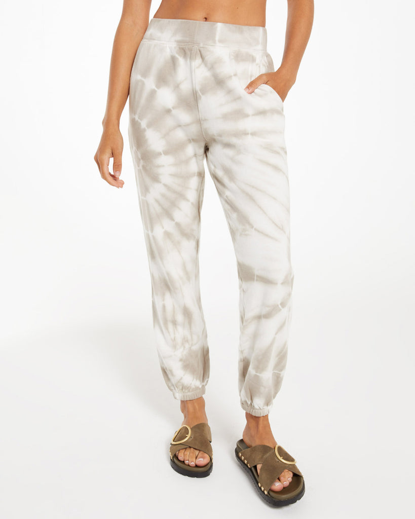model wearing tie dye jogger sweatpants in white and taupe with brown sandals
