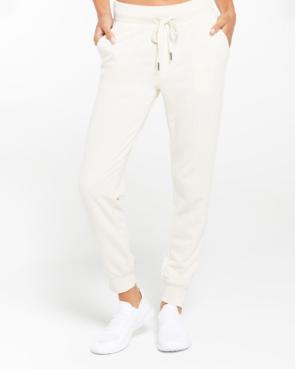 model wearing white jogger sweatpants with white sneakers