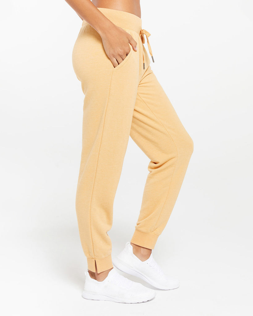 side view of model wearing yellow jogger sweatpants with white sneakers