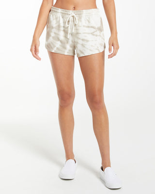 model wearing tie dye shorts in white and taupe with white sneakers