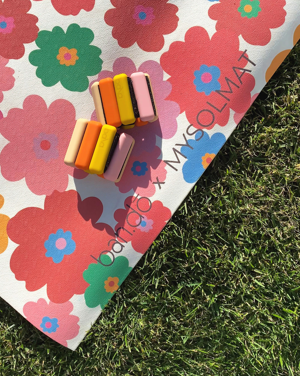 exercise mat with multi-colored, all-over daisy pattern shown with 2 multi-colored Bala ankle weights on grass background