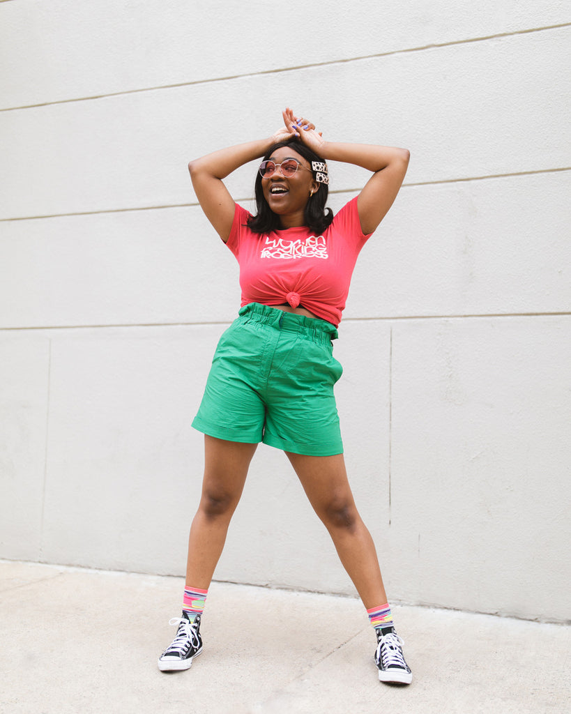 "woman wearing pink tshirt with ""Women Making Progress"" text graphic with green shorts and black sneakers"