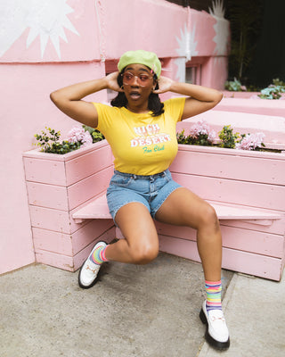 "woman sitting on a pink bench wearing yellow tshirt with ""High Desert Fan Club"" text graphic with blue jean shorts and white shoes and multicolor socks."