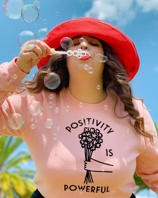"woman blowing bubbles wearing a pink sweatshirt with ""Positivity is Powerful"" text graphic and red hat"