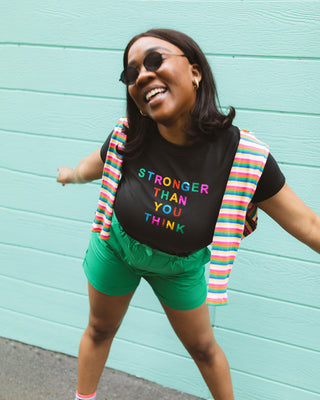 "woman wearing black tshirt with ""Stronger Than You Think"" text graphic with green shorts and sunglasses"