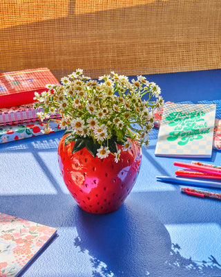 strawberry vase with white flowers on blue surface with desk accessorie scattered throughout