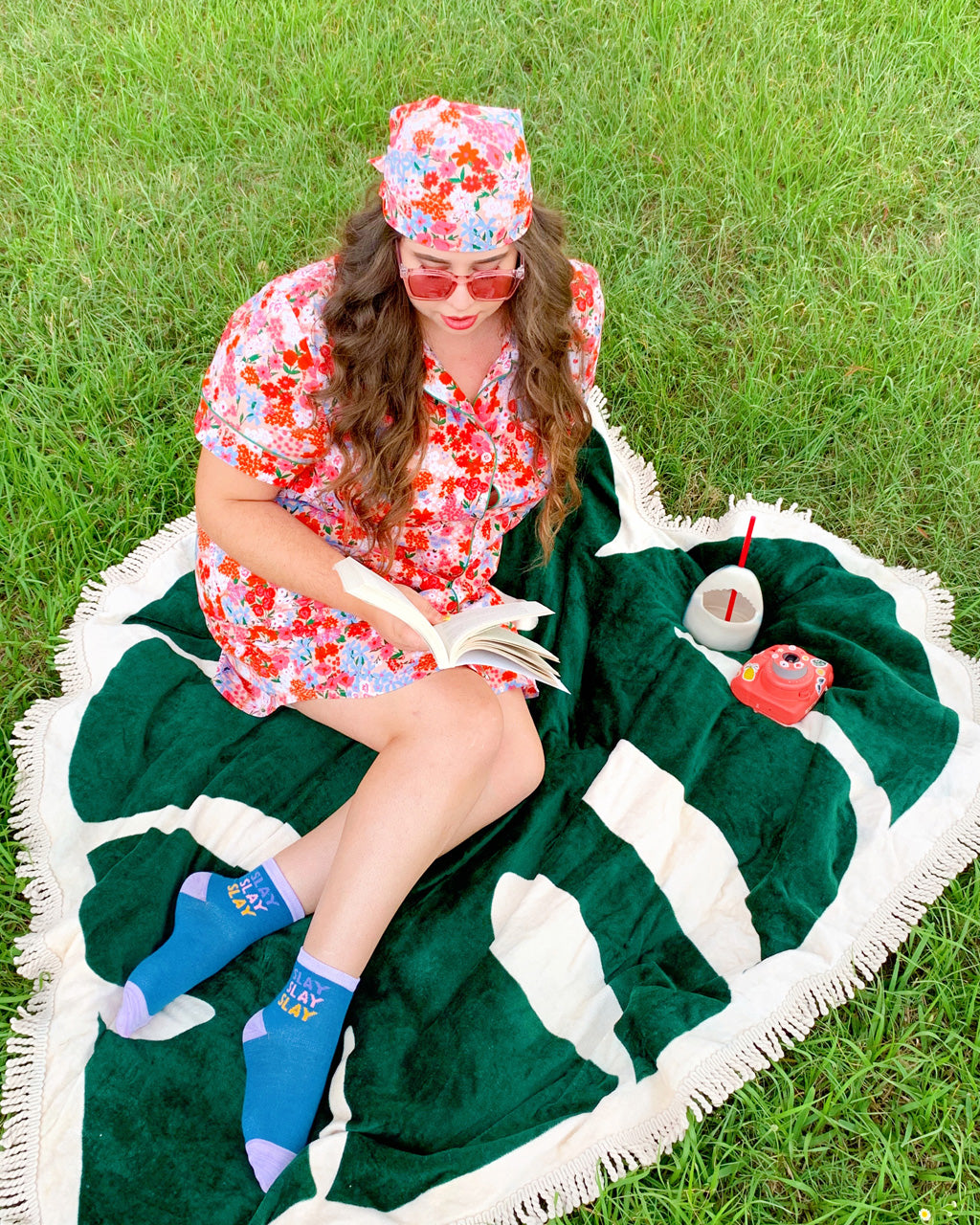 woman wearing short sleeve leisure dress in pink floral with matching bandana tied around her head with blue socks. she is lying on a leaf shaped towel on the grass