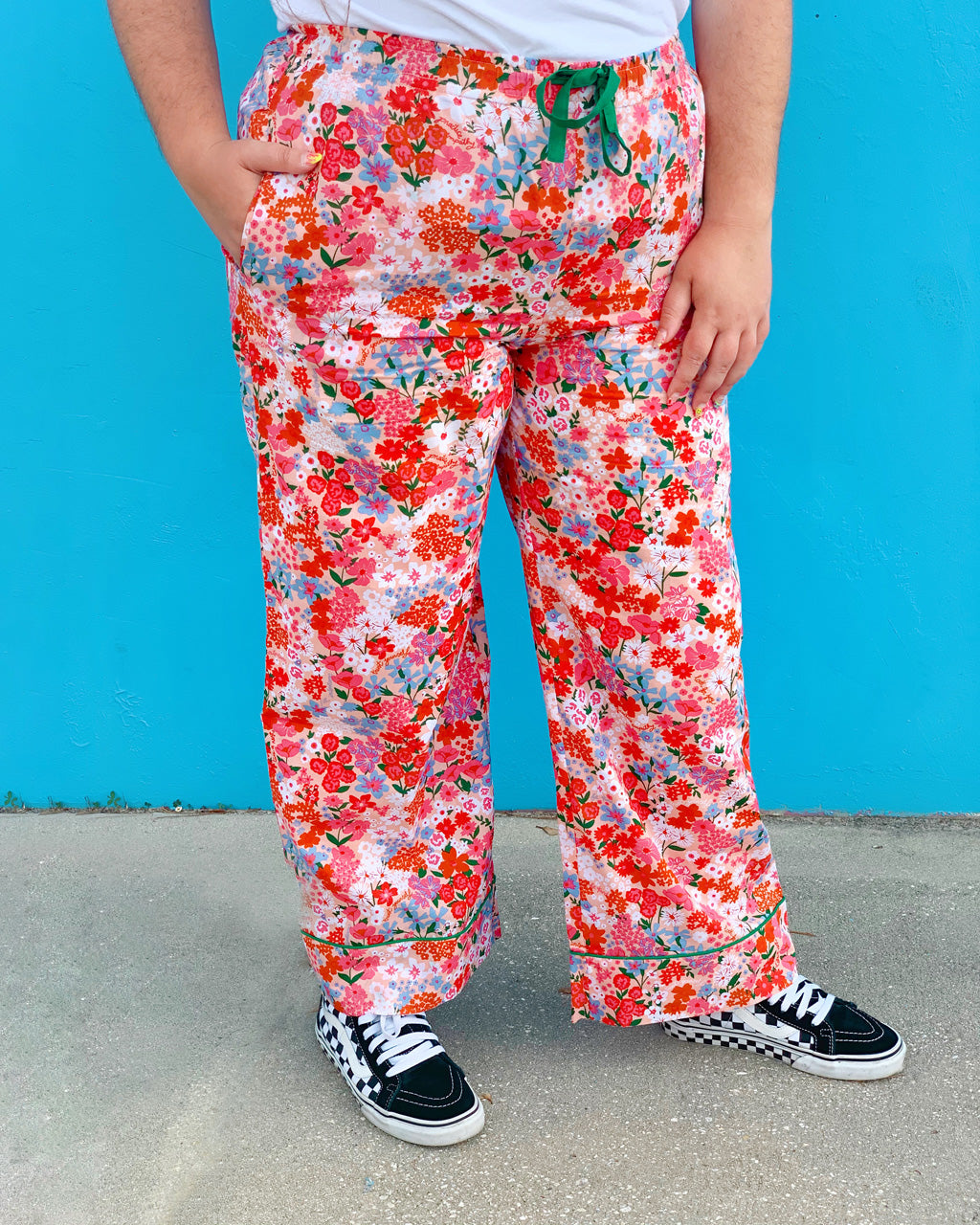 woman wearing bright floral pajama pants with white tshirt and black and white Vans sneakers