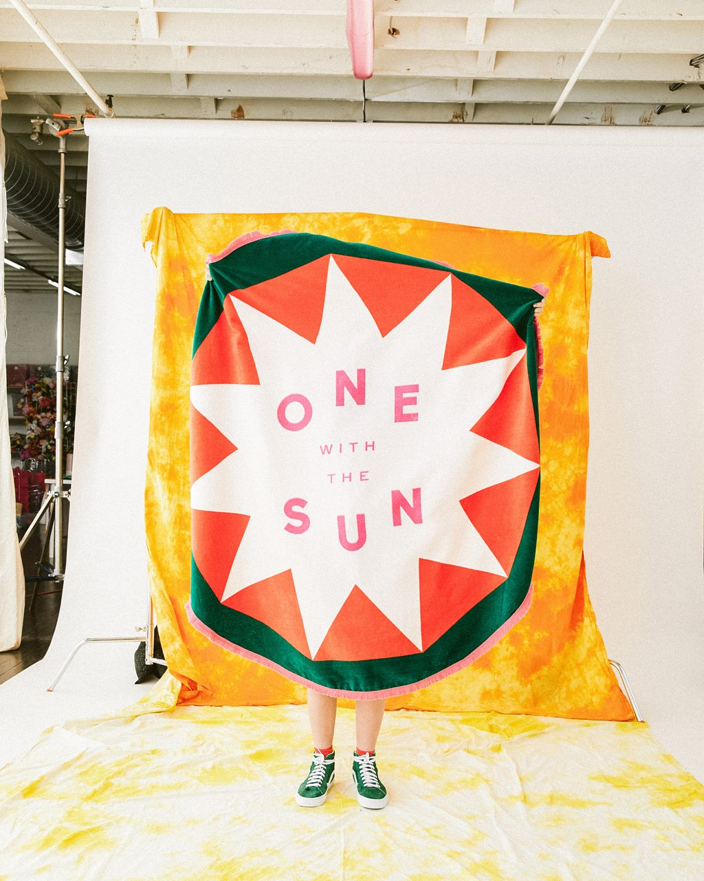 model holding up round beach towel with a sun design and the words on with the sun