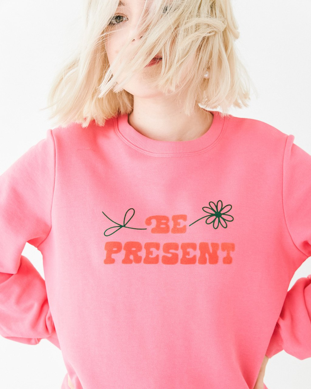 model wearing pink sweatshirt with the words be present on the front with a daisy accent